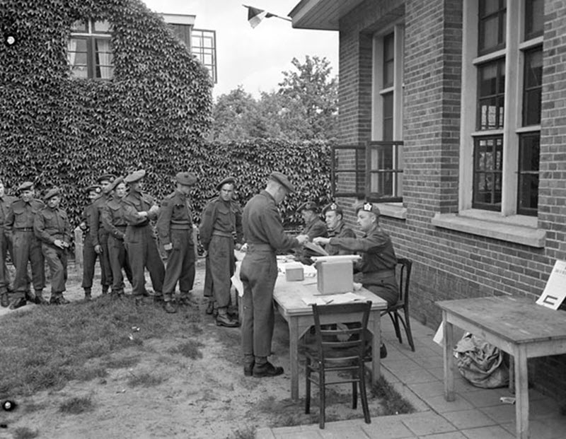 Black and white photo of members of the Canadian military waiting in line to vote at a polling station outside a brick building