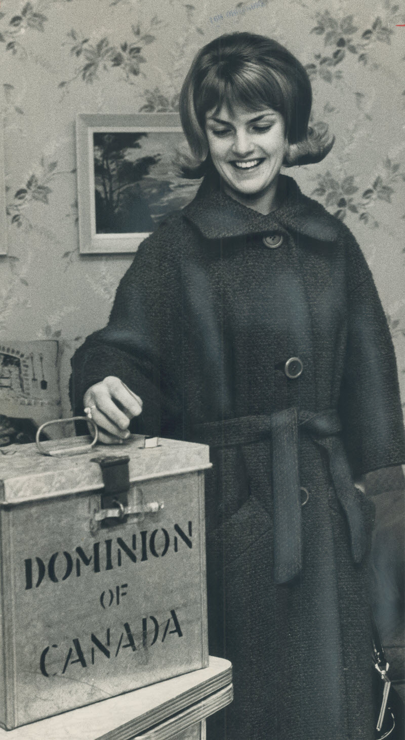 Black and white photo of a young smiling woman placing her ballot in a metal ballot box