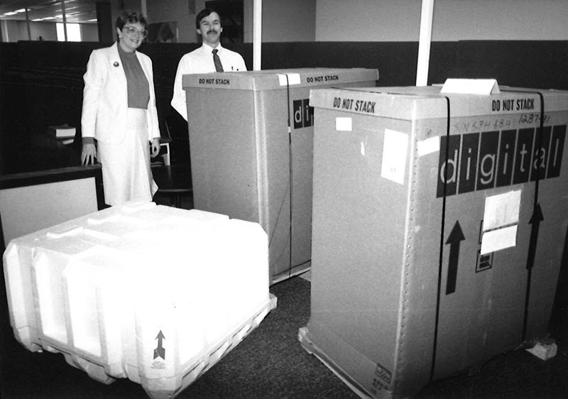 Black and white photo of a woman and a man standing behind two boxes that are nearly as tall as they are, with the word 'digital' written across the front