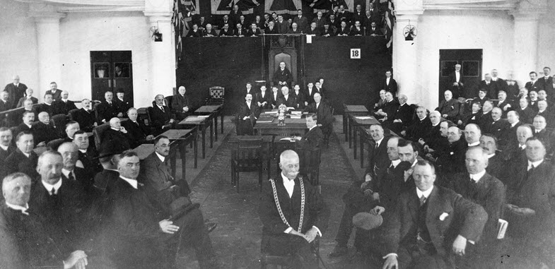 Black and white photo of a spacious hall set up with rows of desks on either side facing inwards. About fifty men wearing suits sit at the desks and look towards the camera