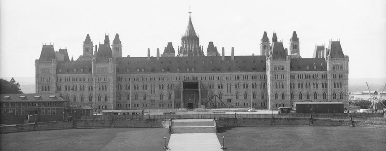 Black and white photo of long, symmetrical building with four stories of arched windows and a main entrance at its centre