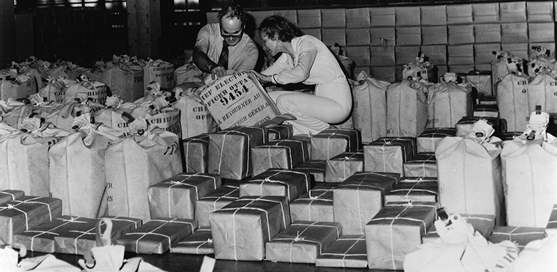 Black and white image of a man and a woman crouching down in a room that has dozens of packages and canvas mail bags lined up in horizontal rows. They partially lift one of the canvas bags to get a better look