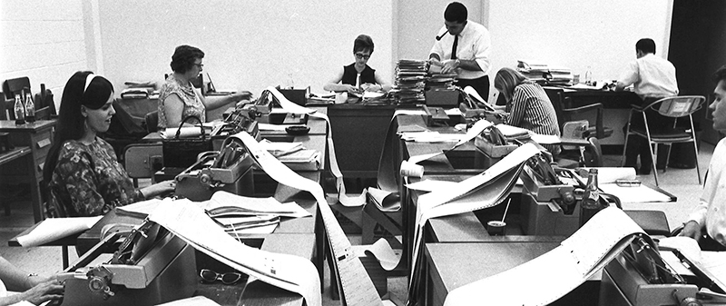 Black and white image of half a dozen workers in an office seated at typewriters with large rolls of paper spilling out over their desks