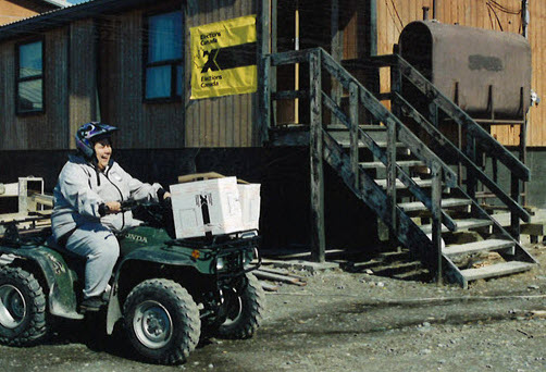 A man rides an all-terrain vehicle with a ballot box attached to the front past a small wooden building with an Elections Canada sign on its side
