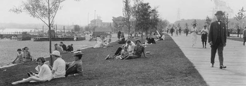 Small groups of people sitting on the grass along the Toronto waterfront in 1920. A few trees scatter the shoreline. A man in a suit and boater hat strolls down a boardwalk beside the grass
